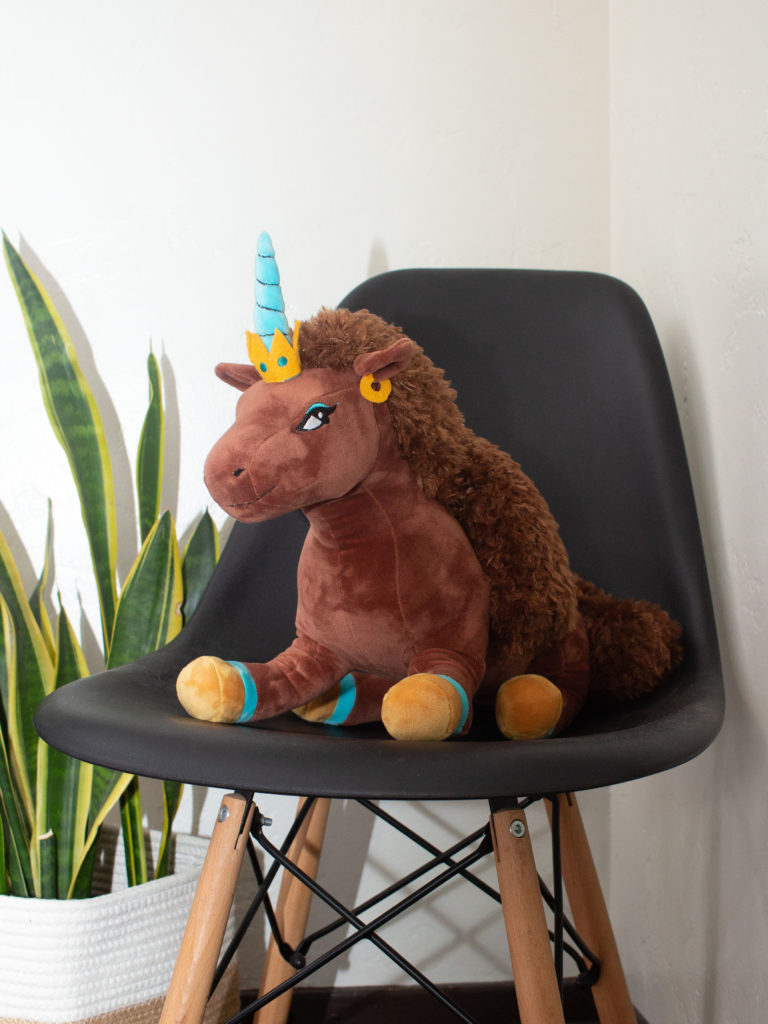 Afro-unicorn plushie in a chair